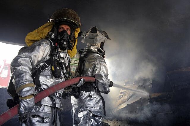 Zwei Feuerwehrmänner löschen einen Brand