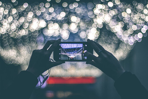 Frau fotografiert mit einem Handy in eine Lichtquelle
